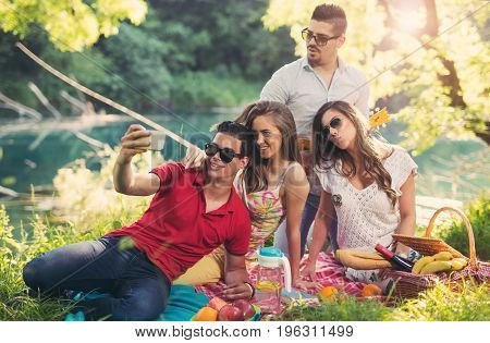 Young people having picnic near the river. Young friends relaxing by the river