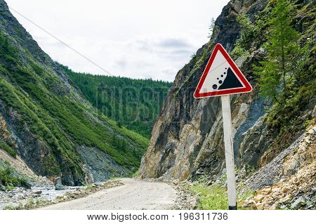 A landslide warning road sign in the mountains