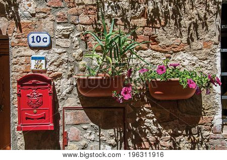 Close-up of mailbox of the post office and flower pots in Colle di Val d'Elsa. A graceful village with its historic center preserved and known by its crystal production. Located in the Tuscany region