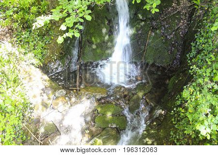 Waterfall Falling Over A Stream Between Trees And Algas