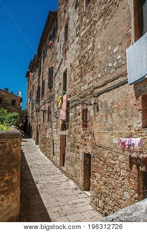 View of narrow alley with old buildings and lamps in Colle di Val d'Elsa. A graceful village with its historic center preserved and known by its crystal production. Located in the Tuscany region