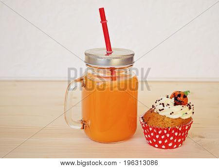 Big jar with orange juice and cupcake for halloween party. Halloween decoating concept for food