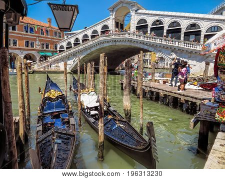 Venice Italy - June 20 2017: Gondolas moored against Rialto bridge in Venice Italy. Venice Grand Canal.