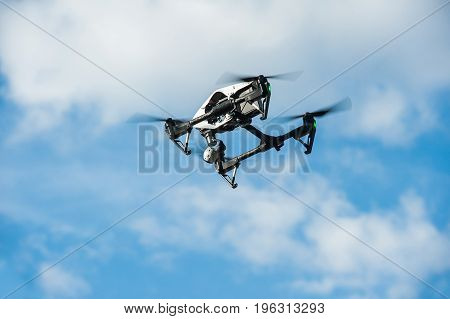 Drone with camera flies in sky on clouds background