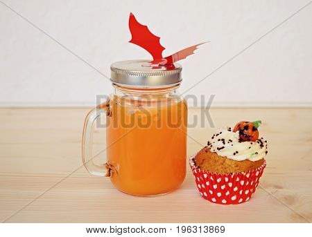 Big jar with orange juice and cupcake for halloween party and red bat. Halloween concept for food