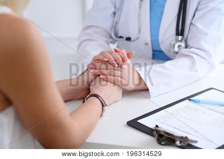 Close up of doctor hands reassuring her female patient. Medicine, help and health care concept