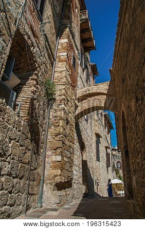 View of narrow alley with old buildings, arch and woman walking in San Gimignano. An amazing medieval town famous for having several towers in its historical center. Located in the Tuscany region