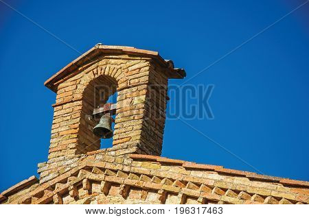 View of bell on top of brick church and blue sunny sky at San Gimignano. An amazing medieval town famous for having several towers in its historical center. Located in the Tuscany region