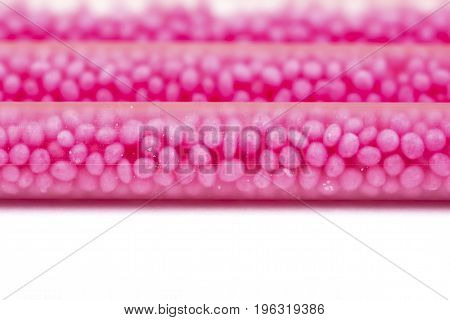 Drinking straws on white background with copy space. Top view of pink eco-friendly straws wiht strawberry balls for summer cocktails.