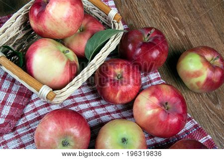 Still life of many apples on a napkin in the basket on a napkin close up