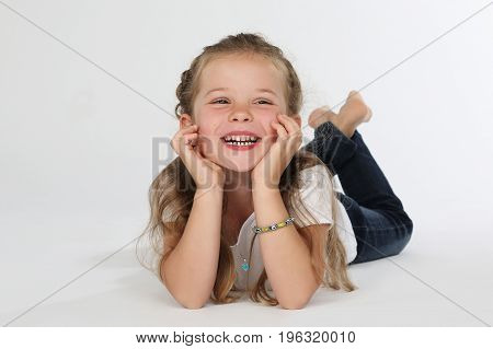 Cute young child barefoot lying on white floor