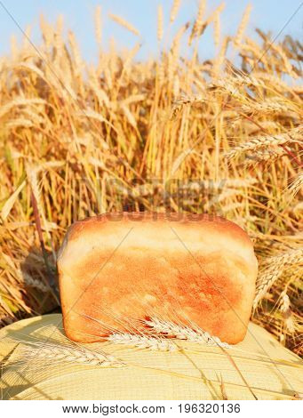 A Loaf Of Bread On The Background Of Ripe Wheat. The Bread On The Background Of Wheat Ears And Blue