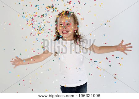 Little girl throwing confetti smiling white background