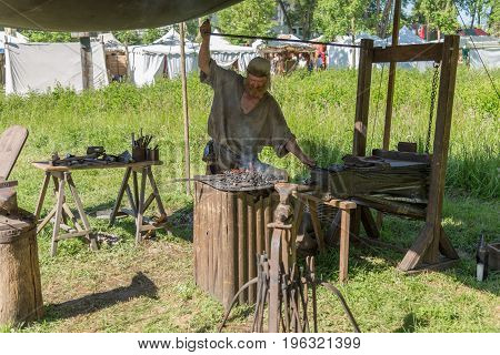 Useldange, Luxembourg, July 6, 2017- Medieval Fair Festival. A medieval blacksmith working on fire during a medieval reenactment festival