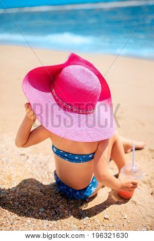 Back view of cute girl with refreshing drink sitting on shore at seaside