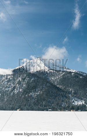 Cloud clinging to a snow capped mountain peak in a blue sky with forested alpine peaks in the foreground