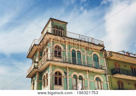 Top of old green multistorey building with balconies and flat roof in traditional architecture design, low angle against cloudy sky