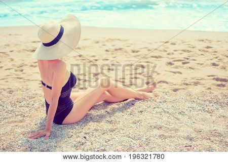 Back view of woman in hat and bikini sitting on sandy shore.