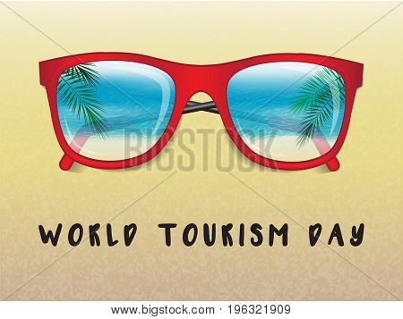 sunglasses on the sand with the reflection of a tropical landscape and the inscription world tourism day