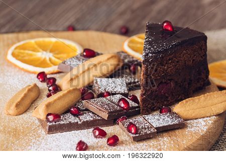 Chocolate cake with pomegranate bitter chocolate and biscuits