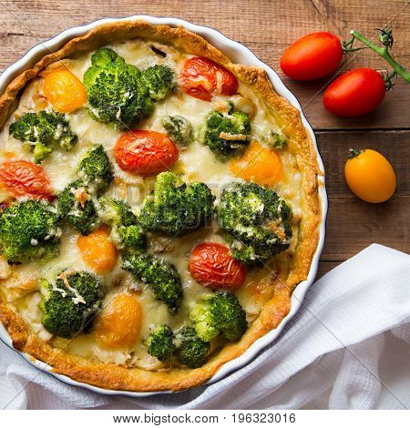 Homemade quiche with red and yellow tomatoes, chicken and broccoli with cheeese