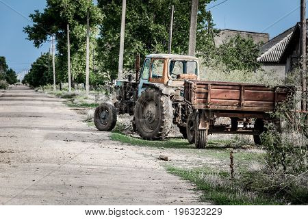 Tractor with a trailer near a rural street road close up
