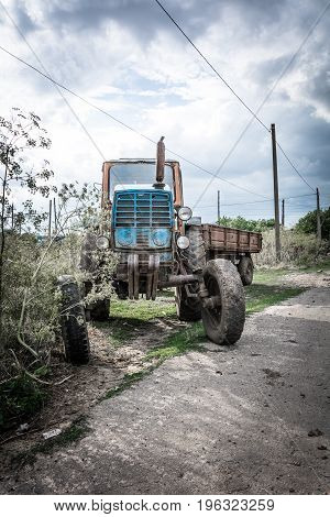 Tractor with a trailer at the road in the evening against a cloudy sky