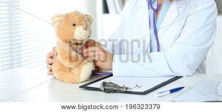 Female doctor examining a Teddy bear  patient by stethoscope. Children medical care concept