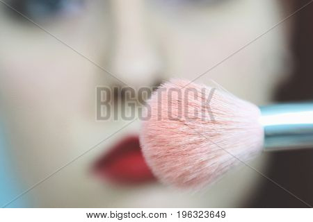 Make Up Vanity 6: a self portrait of a woman holding a makeup brush in front of her face, the woman seems sad or displeased, a shallow depth of field brings attention to the pink brush