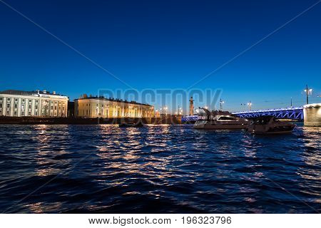 Yachts near the palace bridge and Vasilievsky Island at night in St. Petersburg, Russia
