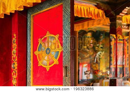 Red colored door of a monastery with artistic Buddhist religious symbol on it Statue of Goutama Buddha seen inside Sikkim Monastery - Sikkim India