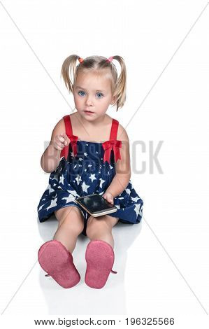 Little beautiful girl sits on the floor, holds a smartphone and points a finger forward at the camera isolated on a white background