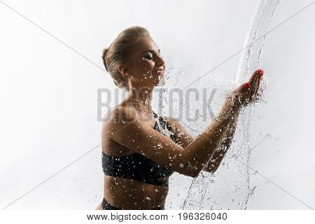 Young happy girl enjoying water stream falling in her hands from above studio shot