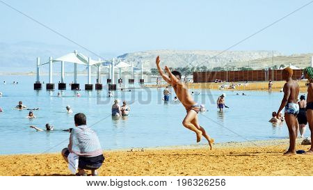 Dead Sea, Israel - May 22, 2017: Interracial Athletes sportsmen acrobats are training and making tricks exercises on the beach.