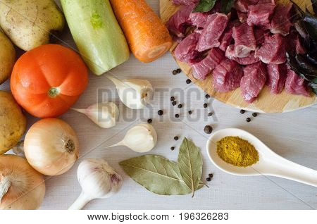 vegetables potato tomato onion garlic and zucchini the beef slices and spices on a white background