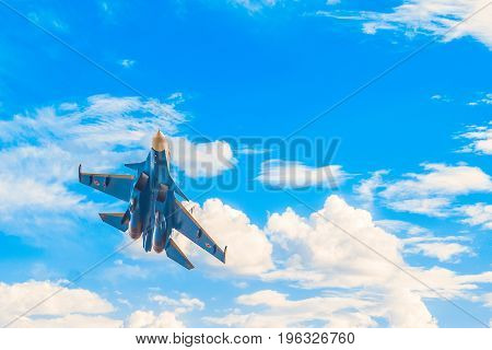 Russian military jet fighter flying in the blue cloudy sky. Background with copy space.