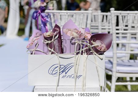 Rose petals in a paper cups in the white box for a wedding celebration