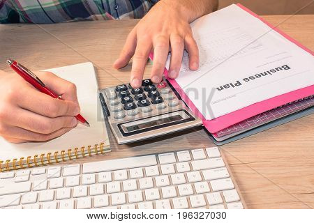Close up Man hand using calculator and writing make note with calculate about cost at home office. The Man and computer are using a calculator on the table in the office room - color / Old Polaroid
