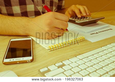 Man hand with calculator at workplace office. Business and accounting concept. A businessman doing some paperwork using his calculator - Retro color
