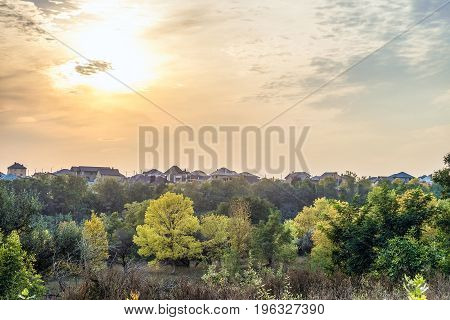 Autumn sunset over the roofs of suburban houses. Evening landscape in backlight sunlight. Belgorod Region Russia.