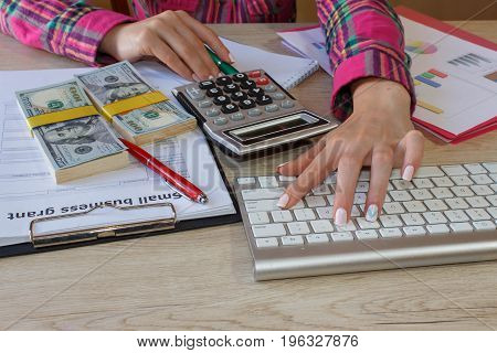 Female with Business plan calculator dollar banknote spreadshee and pen on the table. Young woman working in office sitting at desk using computer