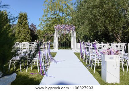 Wedding ceremony in white, violet, blue, pink colors outdoors