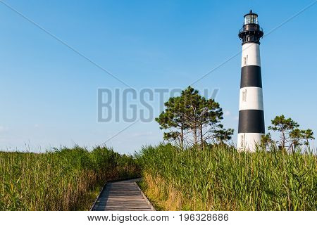 Marshland, with a wooden boardwalk leading to the historic Bodie Island lighthouse on the Outer Banks of North Carolina.
