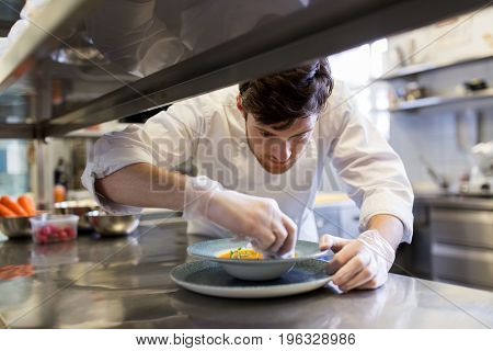 food cooking, profession and people concept - happy male chef cook serving plate of soup at restaurant kitchen