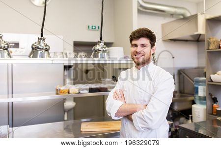 cooking, profession and people concept - happy male chef cook with crossed hands at restaurant kitchen