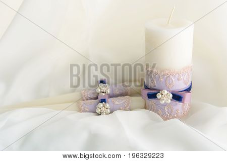 Wedding decorated candles with the bowknots and pearls in tenderly blue and violet colors