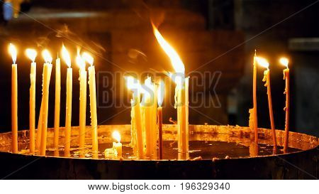 Burning candles in the Holy Sepulcher Church in Jerusalem. The Holy Sepulchre Church and Empty Tomb the most sacred places for all religious Christians in the world.