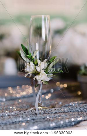 Wedding decorated champagne glass with white flowers and green leaves on the grey cloth, closeup