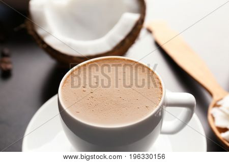 Cup of tasty coconut coffee and nut on table