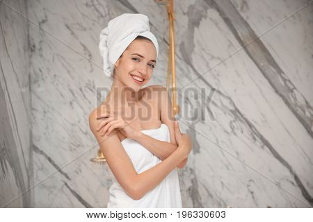 Beautiful young woman after shower in bathroom